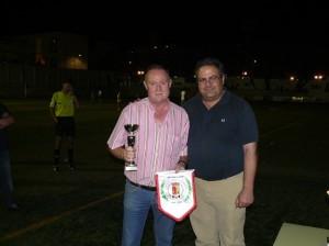 El presidente del Villargordo, Juan Antonio Cañas, recibe el trofeo de manos de Miguel Merino.